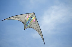 Bat winged kite races across the sky. Kite flies against a blue sky background with white clouds Stock Images