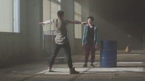 Bataille de danse de deux danseurs de rue dans un bâtiment abandonné près du baril Culture d'houblon de hanche répétition contemp banque de vidéos