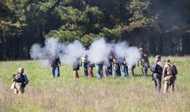 Bataille Reenactors de guerre civile mettant le feu à une volée de fusil photos stock