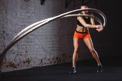 A batalha ropes a sessão Os jovens atrativos couberam e tonificaram o treinamento do desportista no gym imagem de stock royalty free