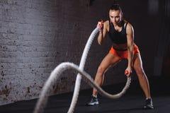 A batalha ropes a sessão Os jovens atrativos couberam e tonificaram o treinamento do desportista no gym imagem de stock