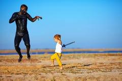 Batalla divertida del niño con el hombre negro Foto de archivo
