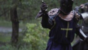 Batalla medieval en el bosque, la gente en armadura que lucha con las hachas y las espadas almacen de metraje de vídeo