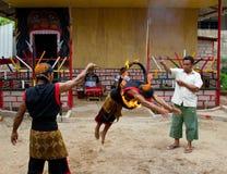 BATAM, INDONESIA - 7 DICEMBRE 2012: Un uomo indonesiano che salta attraverso un anello di fuoco durante la prestazione locale Immagini Stock