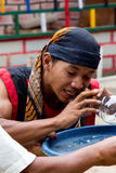 BATAM INDONESIEN - DECEMBER 7, 2012: Lokal medborgare som utför handlingen som äter exponeringsglas i traditionell dress Arkivbilder
