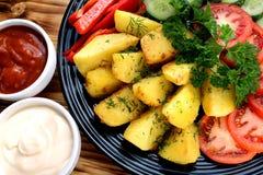 A batata cozeu em um forno com legumes frescos imagens de stock