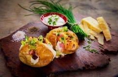 Batata cozida rústica com uma variedade de coberturas Foto de Stock