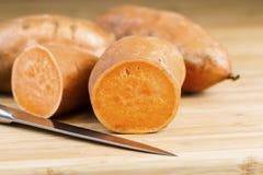 'batata doce' cortado na placa de corte de bambu natural com faca Imagens de Stock