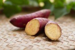 A batata doce japonesa tece sobre o fundo da cesta e da folha fotos de stock