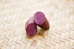 A batata doce roxa tece sobre o fundo da bandeja imagens de stock