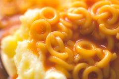 Batata triturada com as aros no molho de tomate Fotos de Stock Royalty Free