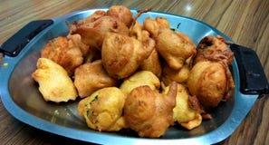 Batata Wada. A closeup click of potato based fresh and fried batata wada snack in a pan royalty free stock images