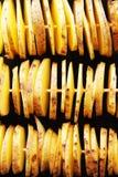 Batatas amarelas cruas em uma casca, corte em fatias As partes são amarradas nos espetos de madeira, apresentados em três fileira Fotografia de Stock Royalty Free