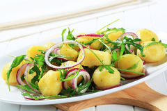 Batatas com arugula e cebola imagem de stock