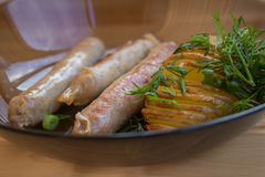 Batatas com as salsichas na grade com ervas Imagens de Stock Royalty Free
