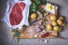 Batatas com ingredientes e carne crua na placa de corte imagens de stock