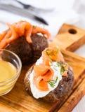 Batatas com manteiga com queijo macio e salmão fumado Fotos de Stock Royalty Free