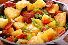 Batatas cozidas com chouriço e ovo frito da salsicha na frigideira imagens de stock royalty free