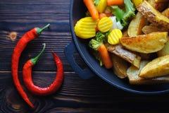 Batatas cozidas com vegetais em uma pimenta da frigideira e de pimentão imagem de stock