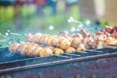 Batatas cozidas em espetos na grade imagens de stock