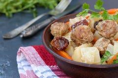 Batatas cozidos com alm?ndegas, cenouras e os tomates sol-secados em uma bacia contra um fundo escuro imagens de stock