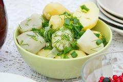 Batatas cozinhadas em um prato redondo Ervas frescas desbastadas Foto de Stock