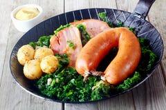 Batatas cozinhadas, Kassler e salsicha na couve imagens de stock royalty free