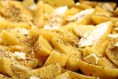 Batatas cruas com as especiarias prontas para ser roasted Fotos de Stock Royalty Free