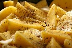 Batatas cruas com as especiarias prontas para ser roasted Fotografia de Stock