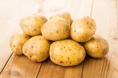 Batatas cruas lavadas montão na tabela Fotografia de Stock