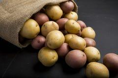 Batatas cruas orgânicas em um saco de serapilheira no fundo da ardósia Fotos de Stock