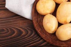 Batatas crus frescas em um fundo de madeira Batatas em uma cesta em um saco de serapilheira Refeições Nutritious Ingredientes do  imagens de stock