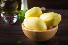 Batatas descascadas e cortadas cruas em uma tabela de madeira resistida velha Fotografia de Stock Royalty Free