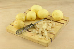 Batatas descascadas e unpeeled com descascador Fotografia de Stock Royalty Free