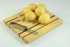 Batatas descascadas e unpeeled com o descascador na placa de corte Fotografia de Stock Royalty Free