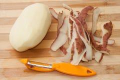 Batatas descascadas frescas em uma placa de madeira da cozinha Fotografia de Stock