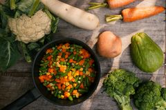 Batatas dos vegetais, cenouras, couve-flor, brócolis no potenciômetro no wo Fotografia de Stock Royalty Free
