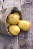 Batatas em um saco na tabela Imagens de Stock