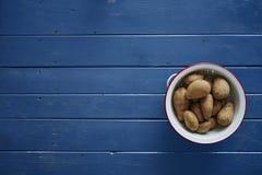 Batatas em uma peneira branca na tabela azul fotos de stock royalty free