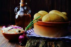 Batatas fervidas em um potenciômetro de argila com couve conservada Imagens de Stock