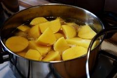 Batatas frescas de um corte no potenciômetro de cozimento de aço Imagens de Stock