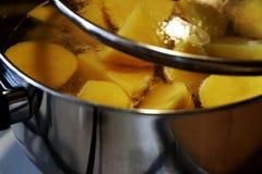Batatas frescas de um corte no potenciômetro de cozimento de aço Fotografia de Stock Royalty Free
