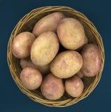 Batatas frescas na cesta no fundo azul velho Imagem de Stock Royalty Free