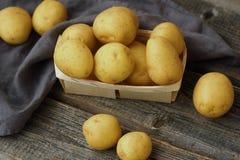 Batatas frescas saborosos em uma cesta de madeira na tabela Fotos de Stock