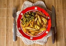 Batatas fritadas com ervilhas verdes Fotos de Stock Royalty Free