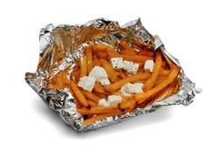 Batatas fritas com as partes de queijo de feta, embaladas na folha, isolada no fundo branco imagens de stock royalty free