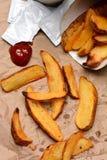 Batatas fritas com ketchup no saco de Brown Fotos de Stock