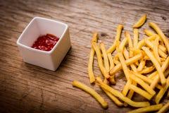 Batatas fritas e ketchup na tabela de madeira Fotografia de Stock