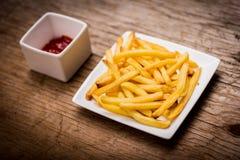 Batatas fritas e ketchup na tabela de madeira Imagem de Stock Royalty Free