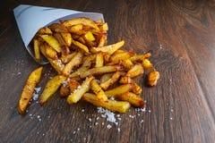 Batatas fritas em um saco de papel com molhos na terra traseira de madeira foto de stock royalty free